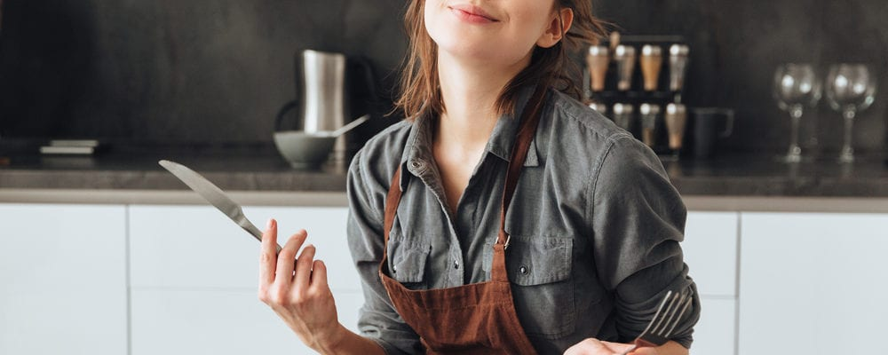 A woman slowly enjoying her meal and practicing mindful eating tips to take control of her hunger and appetite. Here are mindful eating tips to get you started!